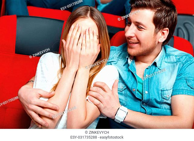 I am afraid. Young woman shielding her eyes with her hand in cinema and her male friend trying to calm her down
