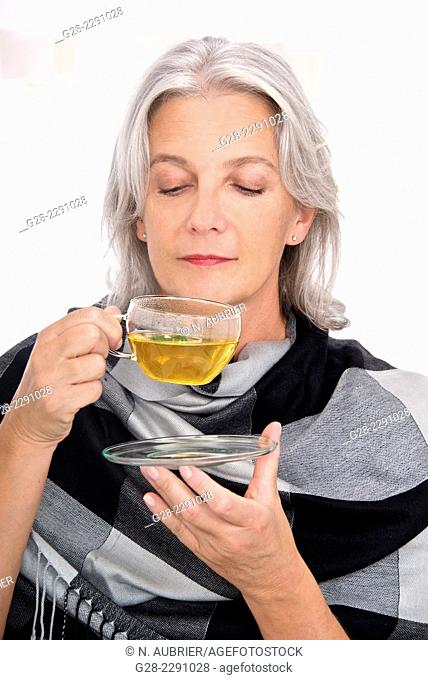 Beautiful senior woman holding a glass cup of tea and about to drink