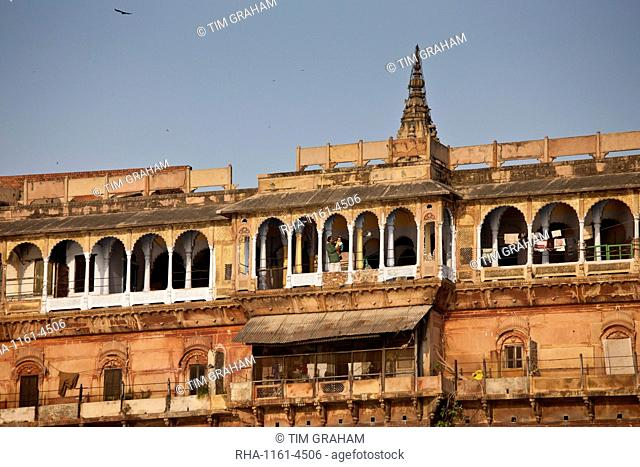 Man holding child in ancient building fronting the famous Ghats by The Ganges River in Holy City of Varanasi, India