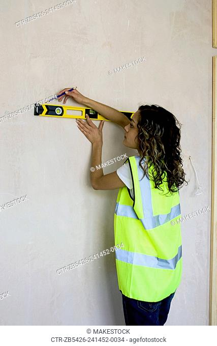 Young woman using a spirit level on a construction site