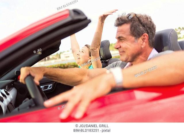 Caucasian couple driving convertible