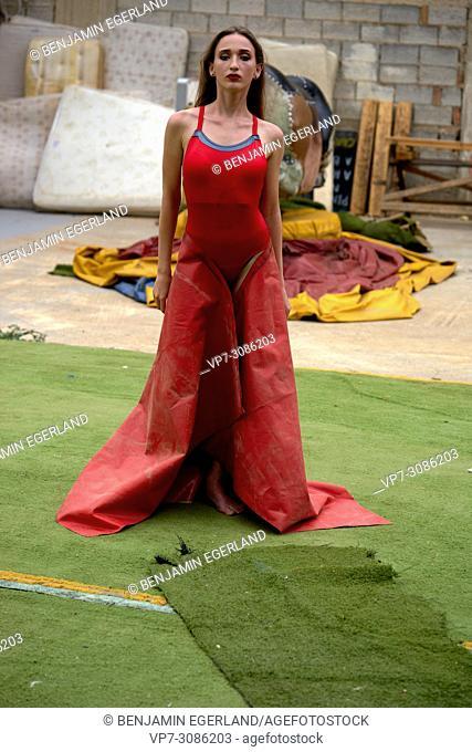 fashion model woman using red tarpaulin as dress in backyard, fashion, thoughtful, fashion criticism