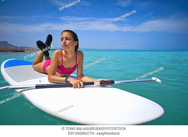 Girl relaxed lying on paddle surf board SUP relaxed in summer
