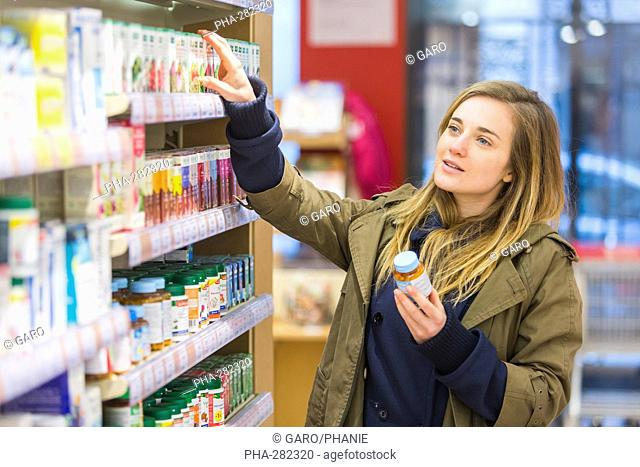 Woman shopping for phytotherapy products in bio supermarket