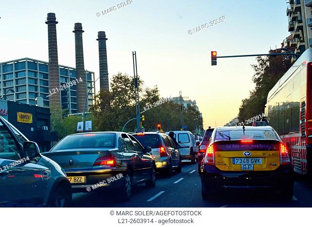 Cars in row waiting at a red light near Three Chimneys, old textile industrial complex, nowadays Fecsa Building. Barcelona, Catalonia, Spain