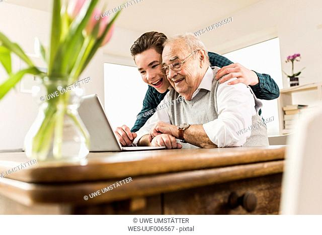 Senior man and his grandson looking together at laptop in the living room