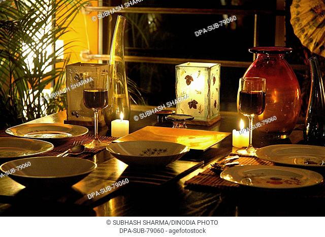 Red wine in glasses , candles , table setting for cozy intimate romantic candle light dinner , mellow mood