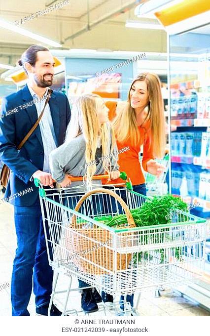 Familie fährt einen Einkaufswagen durch den Lebensmittelmarkt