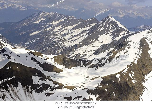 aerial shot, from a small plane, of melting ice and late spring snow on Moro lake, shot on a bright springtime day in Orobie mountains, Bergamo , Italy