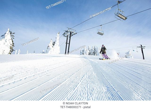 Mid-adult woman on ski slope under cable car