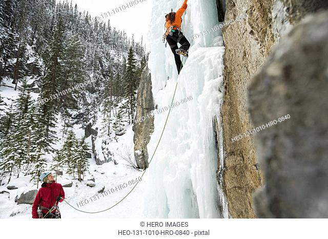 Man belaying friend on ice wall in mountains