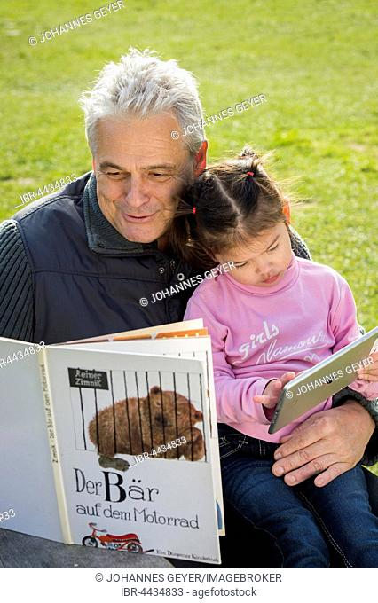 Father reading book to daughter, sitting on meadow, girl playing with tablet, Poing, Bavaria, Germany