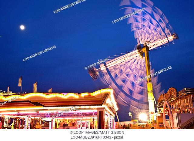 Moving lights of carousel ride helter skelter and vertical ride at fun fair at dusk