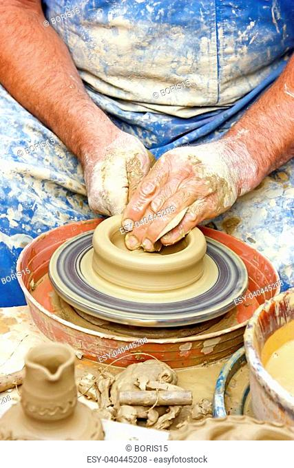 Close up of potter's hands making clay pot