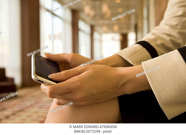 Close up of mixed race businesswoman holding cell phone