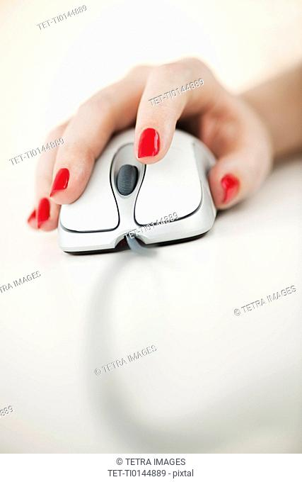 Close up of woman's hand with red nail polish holding computer mouse