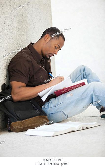 Black college student doing homework outdoor