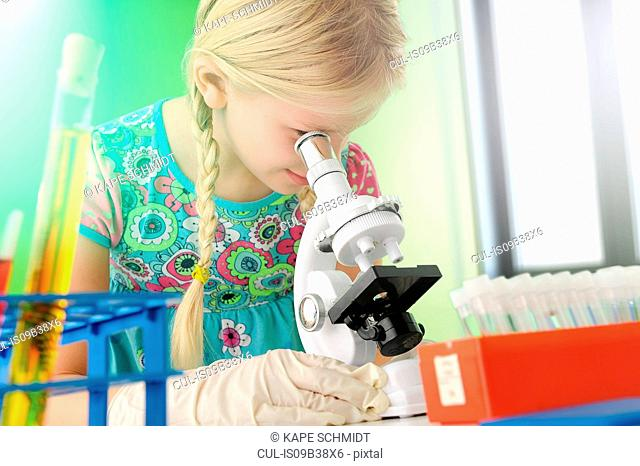Girl pretending to be scientist looking through microscope
