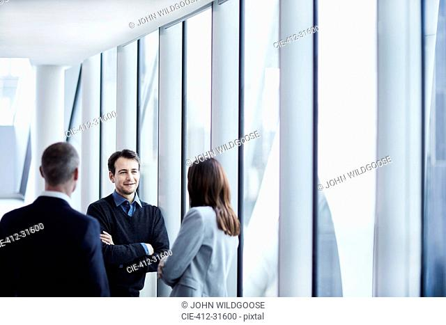 Business people talking at office window
