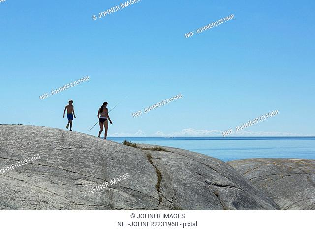 Mother with son walking on rocky coast