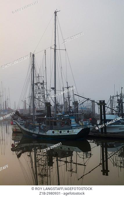 Fishing boats and pleasure craft in Steveston on a foggy morning in Richmond, British Columbia
