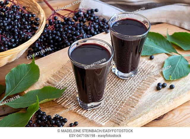Two glasses of black elder syrup with fresh elderberries