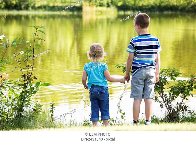 Older brother showing is sister the lake and holding her hand for safety; Edmonton, Alberta, Canada