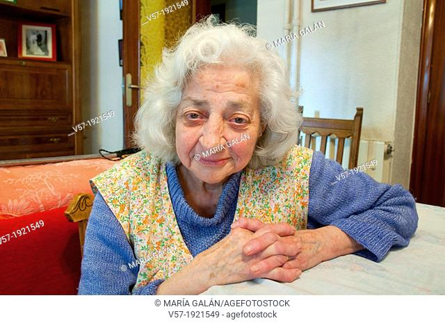 Portrait of elderly woman at home, smiling and looking at the camera