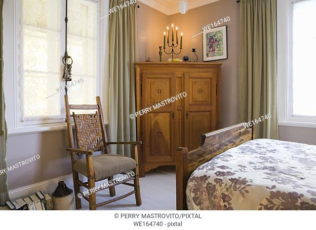 Partial view of double size bed and antique upholstered wooden chair and armoire in a bedroom inside an old 1877 cottage style residential home, Quebec, Canada