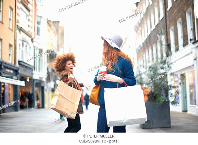 Two young women, holding shopping bags, passing each other in street