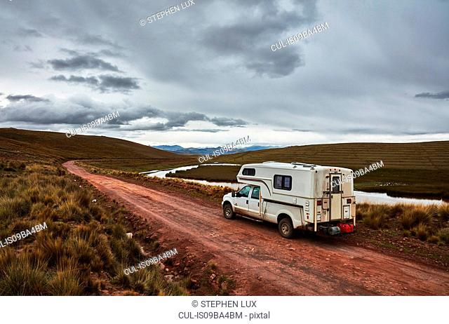Campervan parked on dirt track by river, Yanaoca, Cusco, Peru