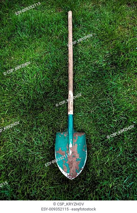 metal green shovel with wooden handle on grass lawn