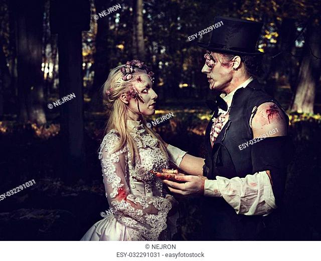 Dressed in wedding clothes romantic zombie man makes a proposal of betrothal to his zombie girlfriend