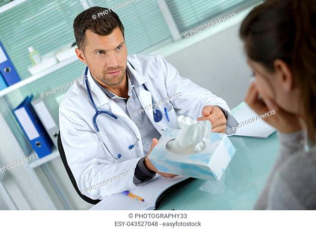 doctor consoling upset woman and passing her a tissue