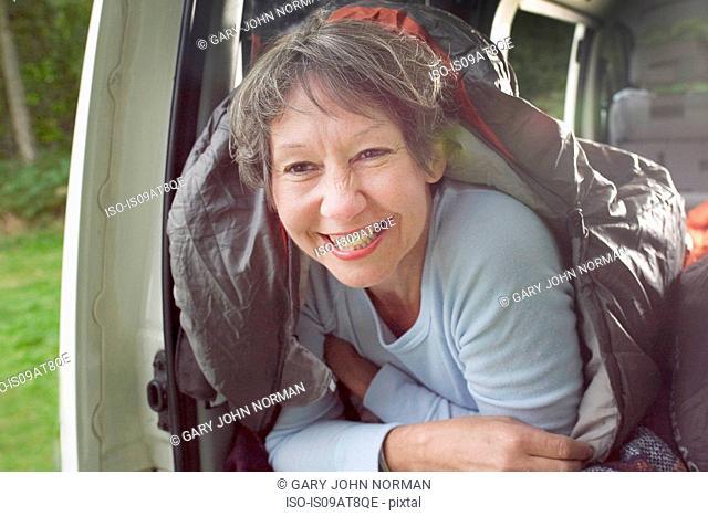 Portrait of senior woman inside sleeping bag, in open camper van