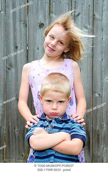 Girl smiling with her brother standing in front of her