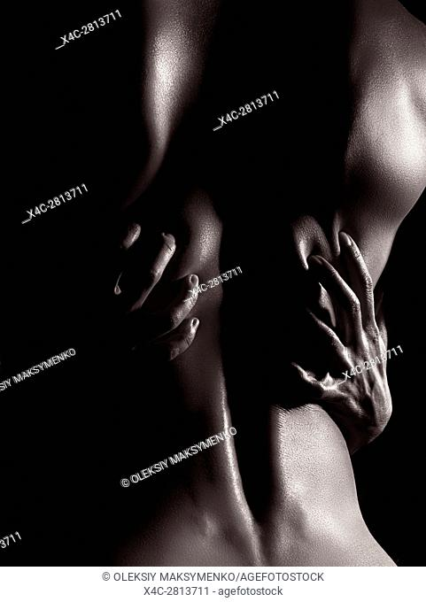 Artistic nude closeup of a sexy bare man back with woman hands grabbing it, black and white fine art body parts abstract photo