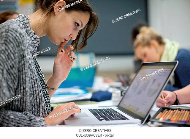 Woman using laptop in art class