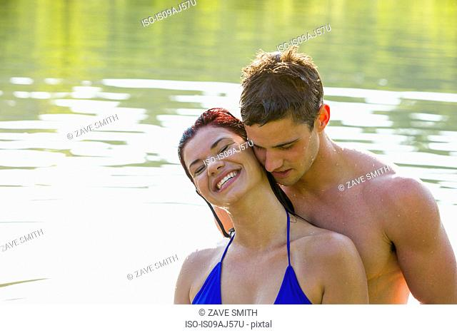 Young couple cheek to cheek in river