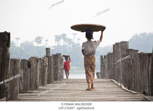 Two Burmese women, seen from behind carrying a basket on their head while walking on the U Beins Bridge in Amarapura near Mandalay, Myanmar, Burma