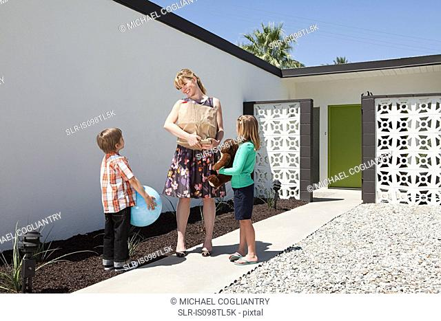 Mother with two children outside home