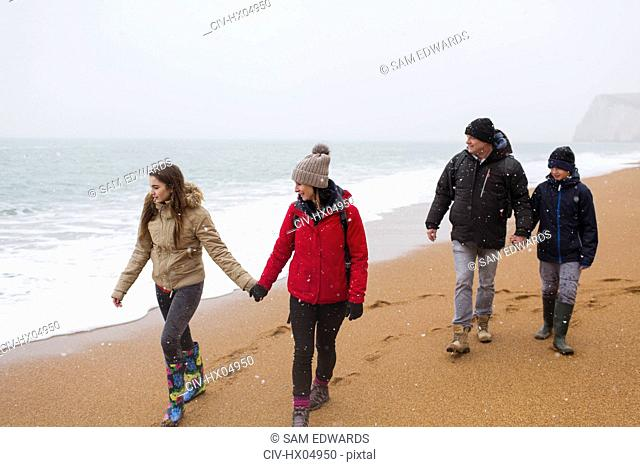 Family in warm clothing walking on snowy winter beach