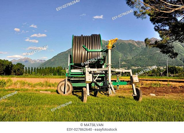 Water sprinkler on the green field with mountain