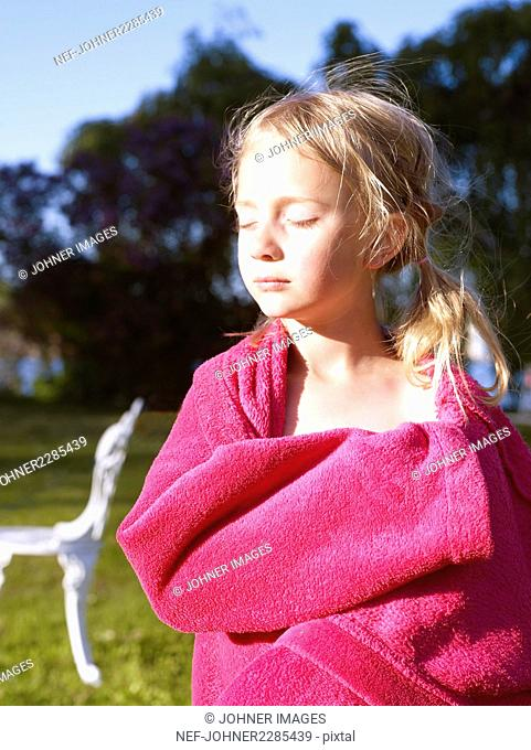 Blond girl wrapped in pink towel