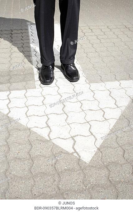 detail of business person standing on pavement with arrow