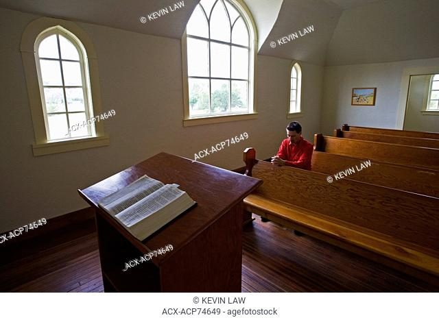 Middle age male praying in United church, Dorothy, Alberta, Canada
