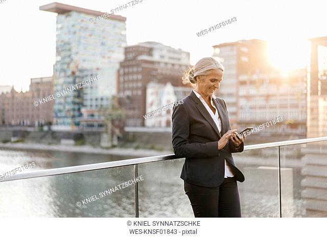 Smiling businesswoman using cell phone on bridge