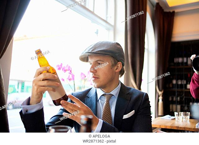 Young gay man looking at beer bottle in restaurant
