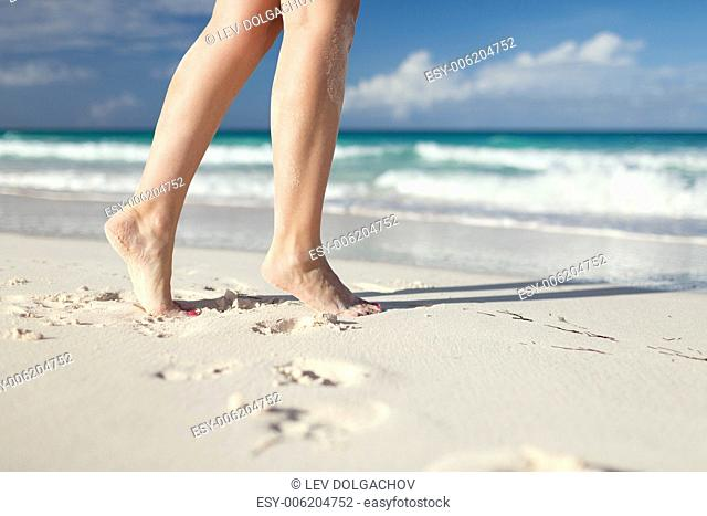 summer, beach, leisure and body part concept - closeup of woman legs on sea shore