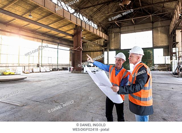 Two men with plan wearing safety vests talking in old industrial hall